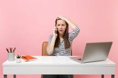 Разочарованная женщина льнуть для того чтобы возглавить говорить на мобильном телефоне для того чтобы получить, что плохую новост стоковое фото