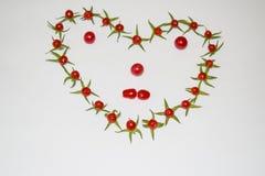 Рамка из помидоров в виде сердца и лица. Frame of small tomatoes in the shape of a heart and face Stock Photography
