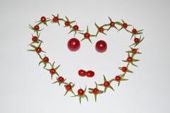 Рамка из помидоров в виде сердца и лица. Frame of small tomatoes in the shape of a heart and face Royalty Free Stock Image