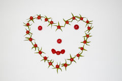 Рамка из помидоров в виде сердца. Frame of small tomatoes in the shape of a heart Stock Photo