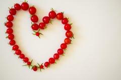 Рамка из помидоров в виде сердца. Frame of small tomatoes in the shape of a heart Stock Photography