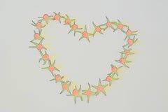 Рамка из помидоров в виде сердца. Frame of small tomatoes in the shape of a heart Stock Image