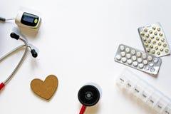 Рамка медицинских инструментов, таблеток, стетоскопа, оксиметра ИМПа ульс, деревянного сердца, волдырей таблеток и контейнера на  стоковое фото rf