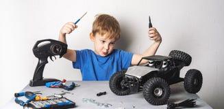 Радио контролировало модели: Мальчик в голубой футболке ремонтирует его багги автомобиля RC стоковое изображение rf