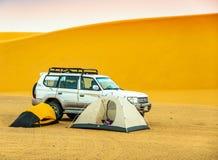 Располагающся лагерем в суданской пустыне с 2 небольшими шатрами, внедорожным кораблем и песчанной дюной на заднем плане стоковое изображение