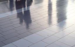 Рассеянные отражения пешеходов идя мраморный тротуар в Дубай стоковое изображение
