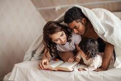 Рассказ молодого чтения семьи интересный волшебный стоковые изображения
