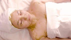 Расслабленная азиатская женщина отдыхая во спа Зеленая косметическая маска основанная на зеленых водорослях cosmetology Тело и ух стоковое изображение