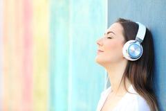 Расслабленная девушка слушая музыку на красочной стене стоковые фотографии rf