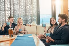 Расслабленные разнообразные друзья в купальных халатах сидя на зоне гостиной бани стоковые фото