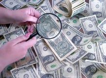 Рассматривает доллары через лупу в руке стоковое фото
