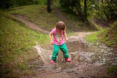 Ребенк скача в лужицу воды стоковые фотографии rf