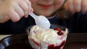 Ребенок есть десерт и выпивая сок в кафе Портрет младенца который ест мороженое сток-видео