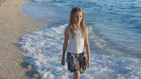 Ребенок играя на пляже на заходе солнца, счастливый ребенк идя в девушку волн моря на взморье стоковая фотография