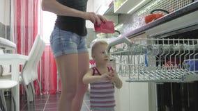 Ребенок помогает матери опорожнить судомойку, случайный образ жизни в интерьере действительности сток-видео