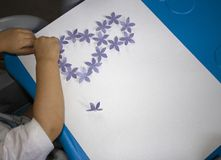 Ребенок делая открытку с изображением 8-ое марта Обработка документов ребенк Материал для творческих способностей детсад стоковая фотография
