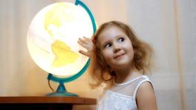 Ребенок смотря на глобусе и мире Ребенок смотрит карту и показывать место будущего путешествия сток-видео