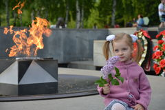 ребенок у мемориального огня. Beautiful child with lilac flower at the Memorial flame, eternal memory to the heroes of the war Stock Photos