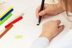Ребенок рисует с покрашенными ручками войлок-подсказки на бумаге стоковые изображения rf