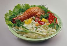 Rice noodles with chicken on a light green plate, decorated with chopped peppers stock photos