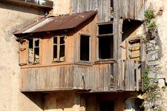 Руины деревянного addon дома с разрушенными досками и пропуская стекла на окнах и с заржаветой крышей ждать быть сокрушенным и стоковые фото