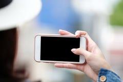 Рука женщины используя умный телефон с пустым экраном над предпосылкой нерезкости, делом и технологией, насмешливым сети онлайн в стоковые фотографии rf