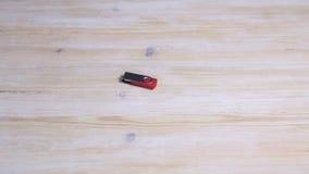 Рука кладет привод USB внезапный на деревянный стол акции видеоматериалы