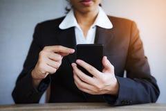 Рука крупного плана бизнес-леди используя умный мобильный телефон на офисе стоковые изображения rf