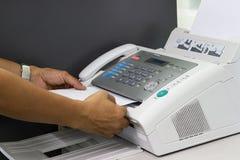 Рука человека использует факс в офисе стоковые изображения rf