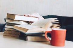 Рука человека принимает книгу на таблице кроватью Много книг и кофе кофе на прикроватном столике стоковые изображения rf