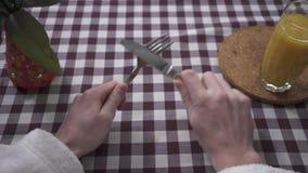 Рука человека трет нож на вилке, требуя еде близко вверх Стекло и ваза апельсинового сока на таблице с видеоматериал
