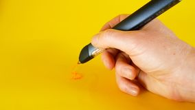 Рука человека рисует с ручкой на желтой предпосылке, идеалом принтера 3d отснятого видеоматериала для тем как нововведение, техно стоковые изображения