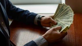 Рука ` s бизнесмена к держать деньги Пригорошня долларов на деревянной предпосылке стоковое изображение rf
