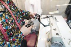 Руки белошвейки отрезали ткань с ножницами на предпосылке швейной машины и рабочего места стоковое изображение