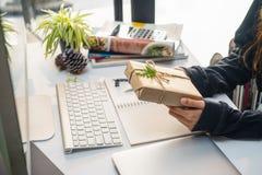 Руки бизнес-леди держа небольшую подарочную коробку на таблице офиса, она смотря подарочную коробку создала программу-оболочку бу стоковые фото