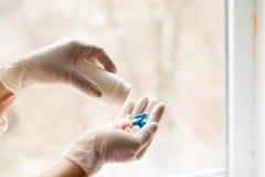 Руки в медицинских перчатках держа различные капсулы стоковое фото