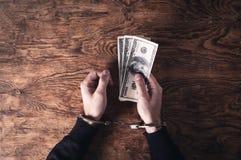 Руки в наручниках держа банкноты доллара развращение стоковое фото rf