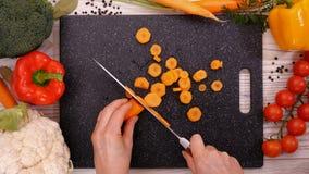 Руки женщины отрезают морковь на прерывая доске сток-видео