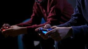 Руки крупного плана предназначенных для подростков мальчиков играя видеоигру сток-видео