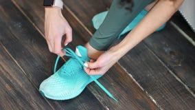 Руки конца-вверх женские шнуруя шнурки на тапках стоя на угле деревянного пола высоком сток-видео