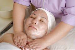 Руки профессионального cosmetologist положили юга мыла на женскую шею пациента Женщина азиатского возникновения с закрытым стоковые фотографии rf