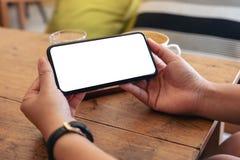 Руки держа черный мобильный телефон с пустым экраном горизонтально с кофейной чашкой на деревянном столе в кафе стоковое фото rf