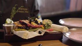 Руки шеф-повара в черных резиновых перчатках положили соусы в зажаренные куски семг рыбы служили с перцем chili, известки и лимон акции видеоматериалы