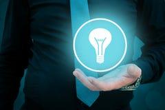Руководитель думает о деле, творческих способностях, зрении дела Электрическая лампочка удерживания бизнесмена в его руке стоковое фото rf