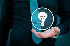 Руководитель думает о деле, творческих способностях, зрении дела Электрическая лампочка удерживания бизнесмена в его руке стоковое изображение