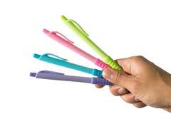 Ручки цвета в руке которые держат совместно много цветов Имеет белую предпосылку стоковая фотография