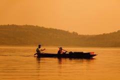 Рыболов гребя для рыб в заходе солнца стоковое изображение