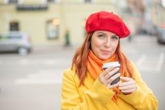 Рыжеволосая молодая женщина в желтом пальто и красном берете выпивает кофе на улице для того чтобы держать теплый стоковые фото