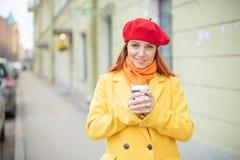 Рыжеволосая молодая женщина в желтом пальто и красном берете выпивает кофе на улице для того чтобы держать теплый стоковая фотография