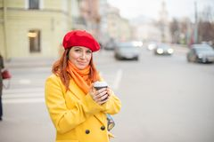 Рыжеволосая молодая женщина в желтом пальто и красном берете выпивает кофе на улице для того чтобы держать теплый стоковые фотографии rf